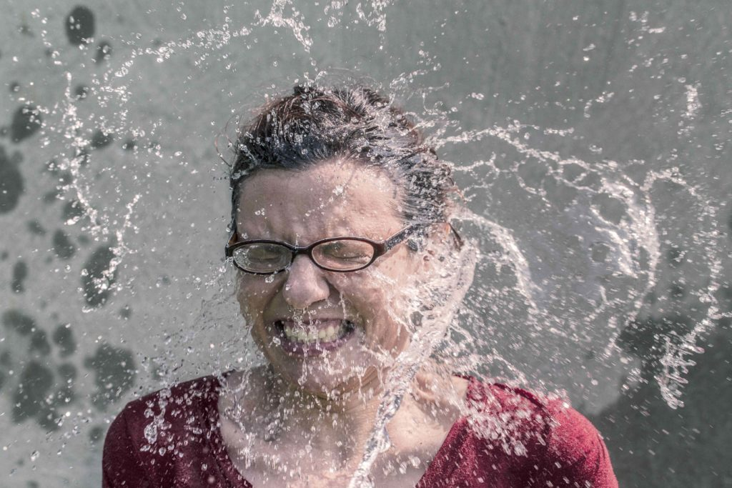 Woman getting water splashed in face